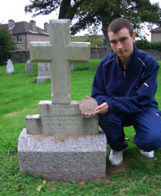 Irish First World War Researcher Conor Dodd at the grave of Canadian Soldier Sergeant Gavin Francis Andrew.  He is holding Gavin Andrew's commemorative plaque.